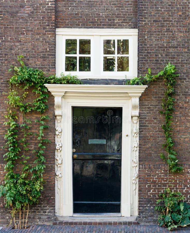 Vieille porte en bois noire avec le cadre blanc sur le mur de briques brun photo stock