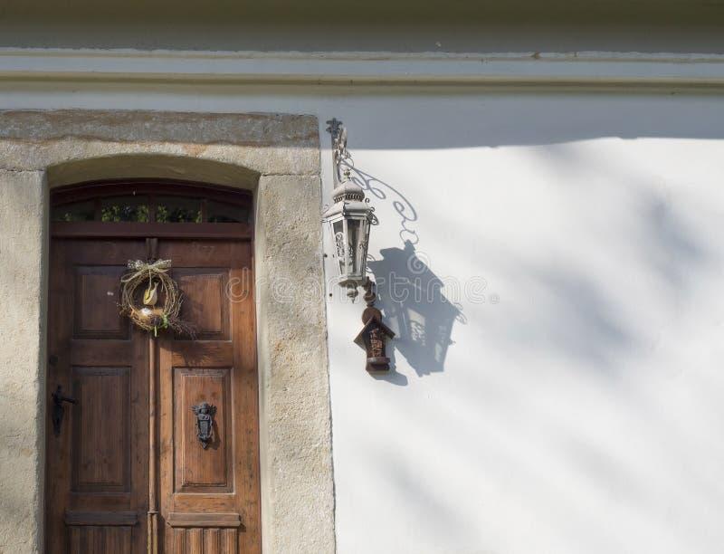 Vieille porte en bois rustique avec la doublure de grès, guirlande, lanterne photographie stock