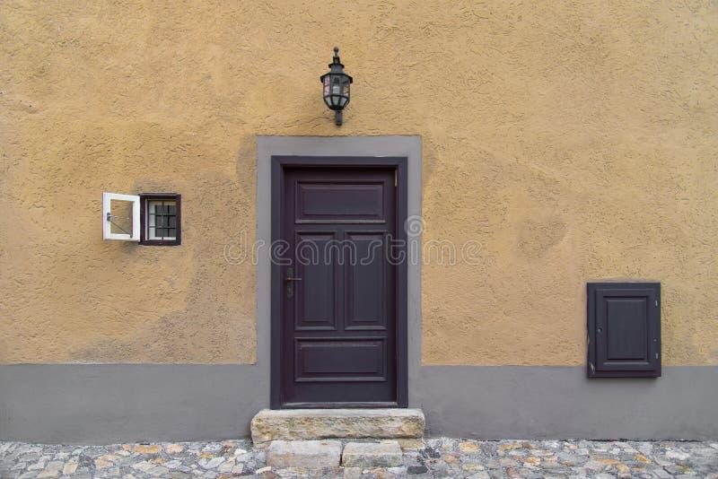 Vieille porte en bois sur le mur jaune en béton W de style rustique de Vieux Monde image stock