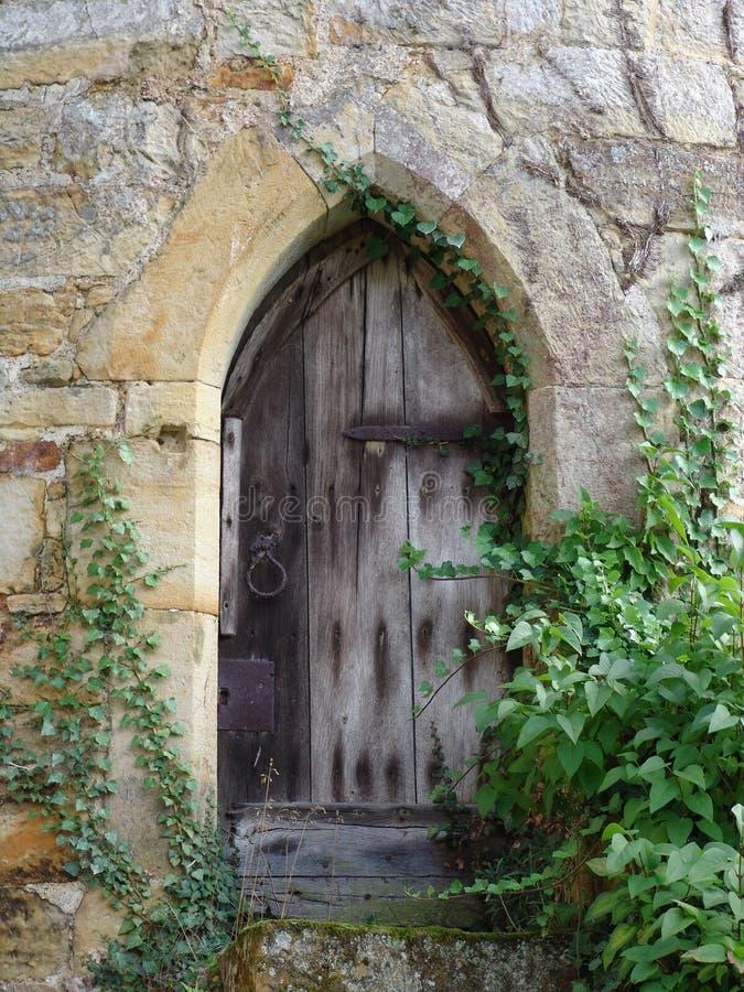 Vieille porte en bois usée dans le mur de château images libres de droits