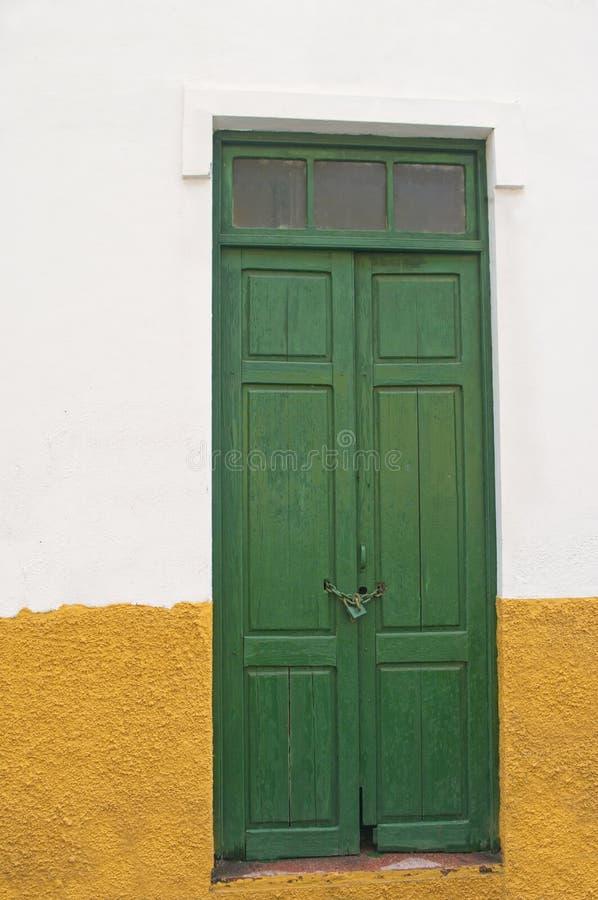 Vieille porte en bois verte européenne dans le mur blanc et jaune photographie stock libre de droits