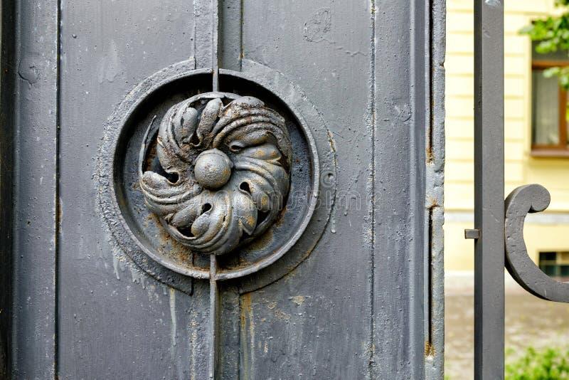 Vieille porte en métal avec la fleur de fer travaillé photos stock