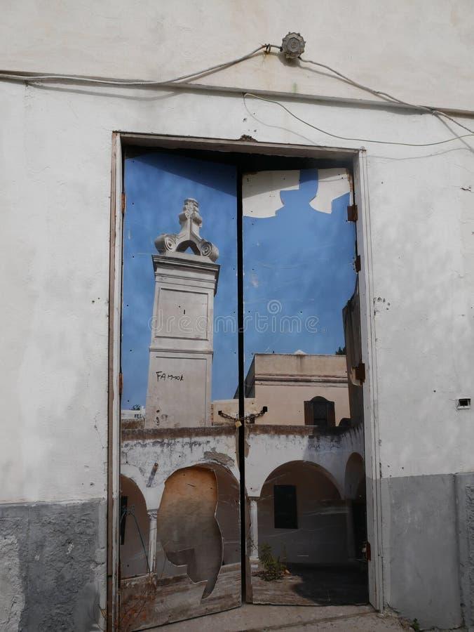 Vieille porte endommagée peinte avec une scène urbaine photos stock