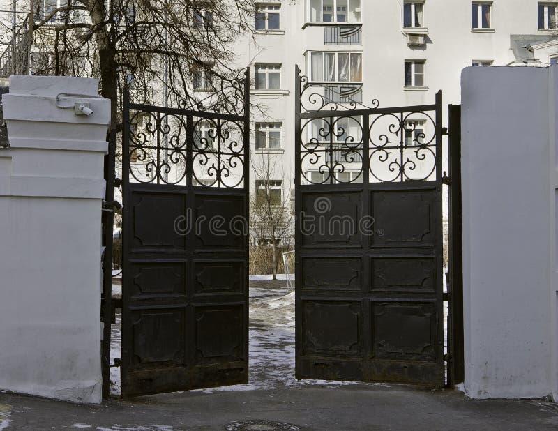 Vieille porte noire d'entrée en métal menant à partir de la rue à la cour de la maison image libre de droits