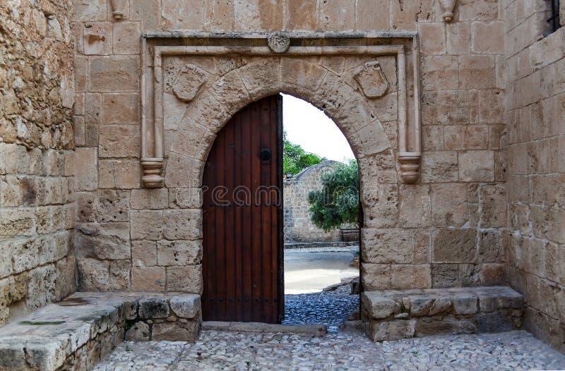 Vieille porte ouverte en bois sur un mur en pierre : une sortie du château photos stock