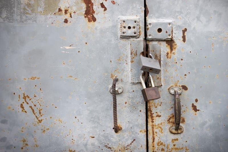 Vieille porte rouillée de fer avec les serrures verrouillées Vieille porte de fer qui est solidement fermée à clef photographie stock libre de droits