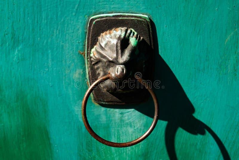Vieille porte verte avec une poignée en forme de lion photographie stock
