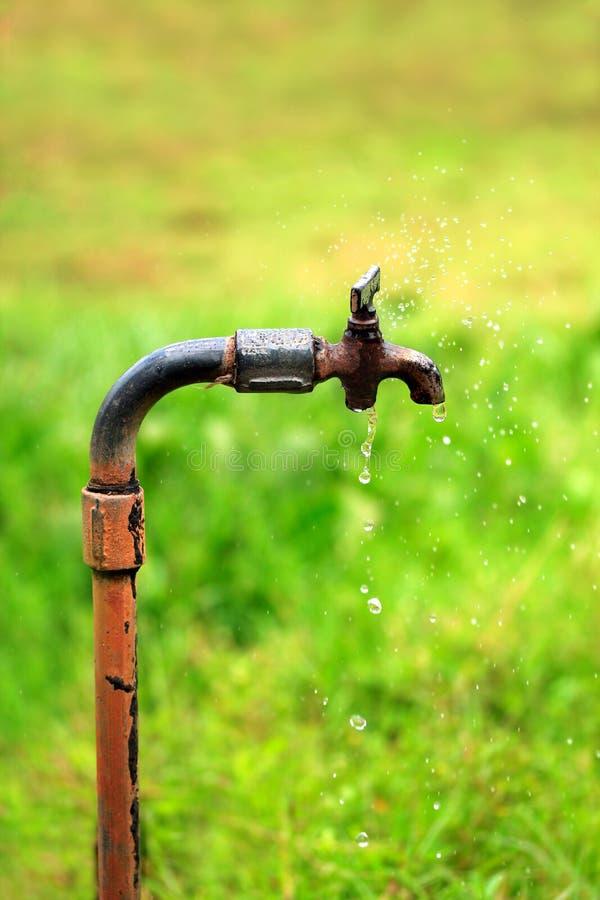 Vieille prise rouillée avec la fuite de l'eau photographie stock libre de droits