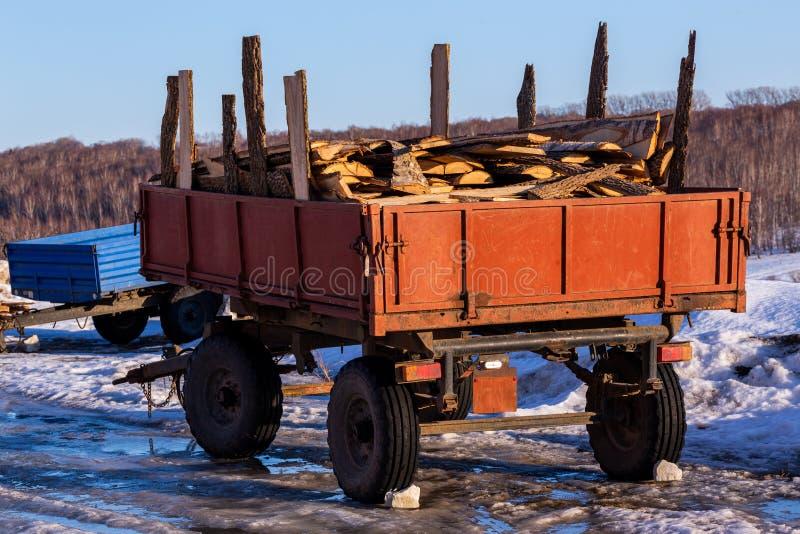 Vieille remorque rustique avec des restes de bois de charpente de bois de chauffage à la lumière du jour d'hiver photos libres de droits