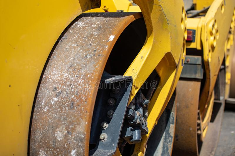 Vieille roue rouillée sale de machine à paver d'asphalte Équipement lourd pour la réparation des routes image libre de droits