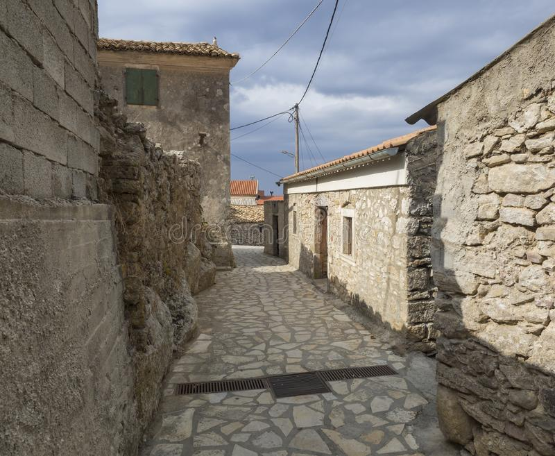 Vieille rue étroite avec les maisons traditionnelles en pierre et pavage au village de Doukades sur l'île Grèce de Corfou photographie stock