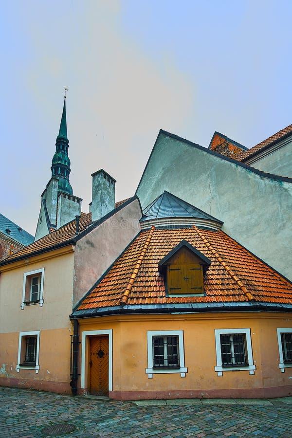 Vieille rue médiévale d'étroit de soirée avec l'église de Peters Lutheran de saint sur le fond à Riga, Lettonie Rétro dénommé photo libre de droits