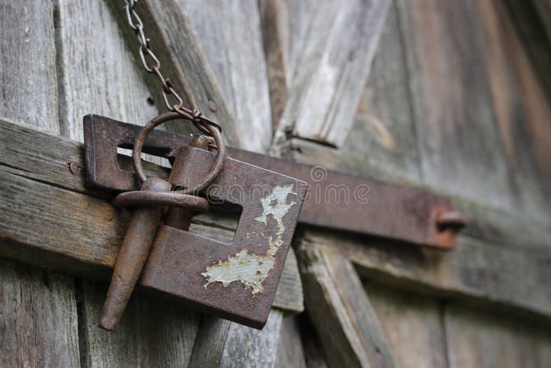 Vieille serrure rouillée sur la porte de grange en bois superficielle par les agents photos stock