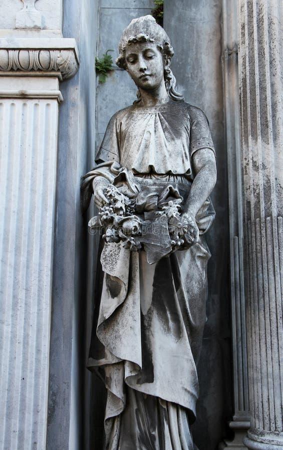 Vieille femme en pierre de statue avec des fleurs sur un cimetière. photographie stock libre de droits