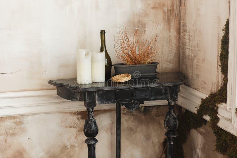 Vieille table basse noire en bois, bougies, pot de fleur de bouteille en verre dans un coin de pièce antique Intérieur et maison  photo libre de droits