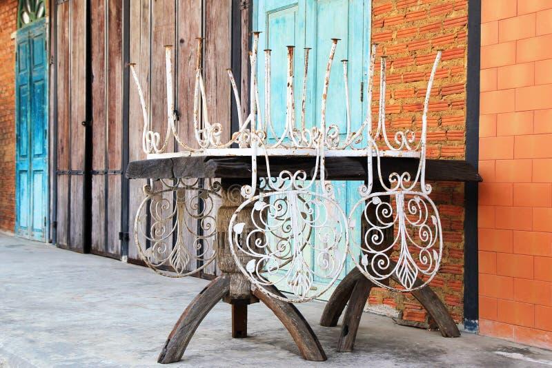 Vieille table en bois avec les chaises blanches de vintage sur un fond de mur de briques et de portes en bois image stock