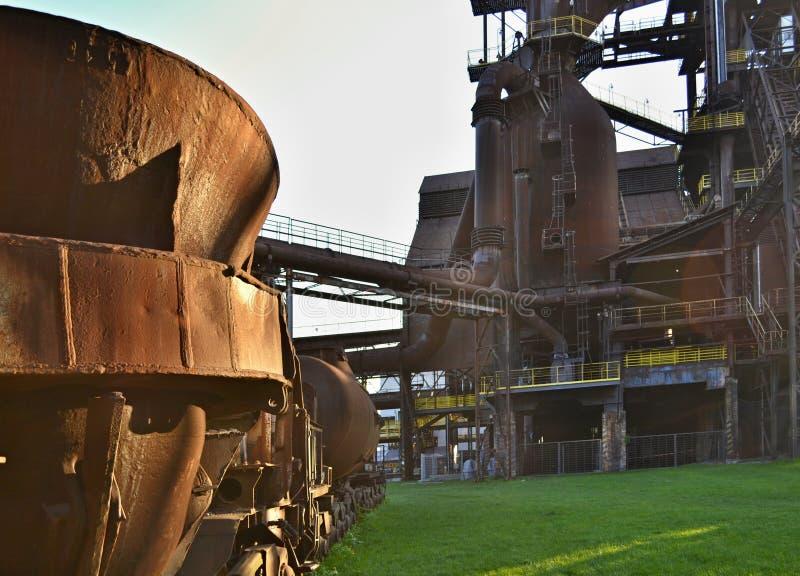 Vieille tasse rouillée pour l'acier de bâti sur un champ vert dans une usine abandonnée de partie métallique photos stock