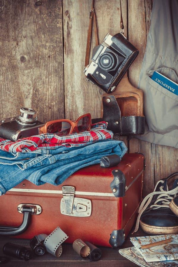 Vieille valise, espadrilles, habillement, lunettes de soleil, cartes, films images stock