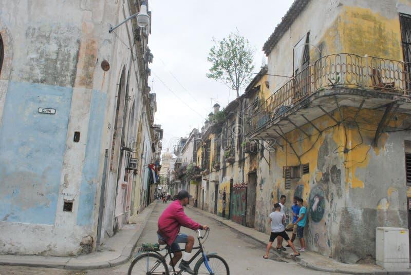 Vieille ville La Havane regardant vers le bas la petite rue avec le cycle d'équitation de l'homme dans le premier plan images libres de droits