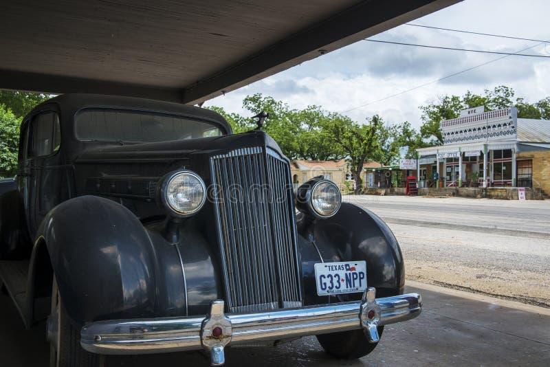 Vieille voiture avec l'épicerie générale et bureau de poste sur le fond dans la petite ville de Hye dans le Texas, Etats-Unis photos stock