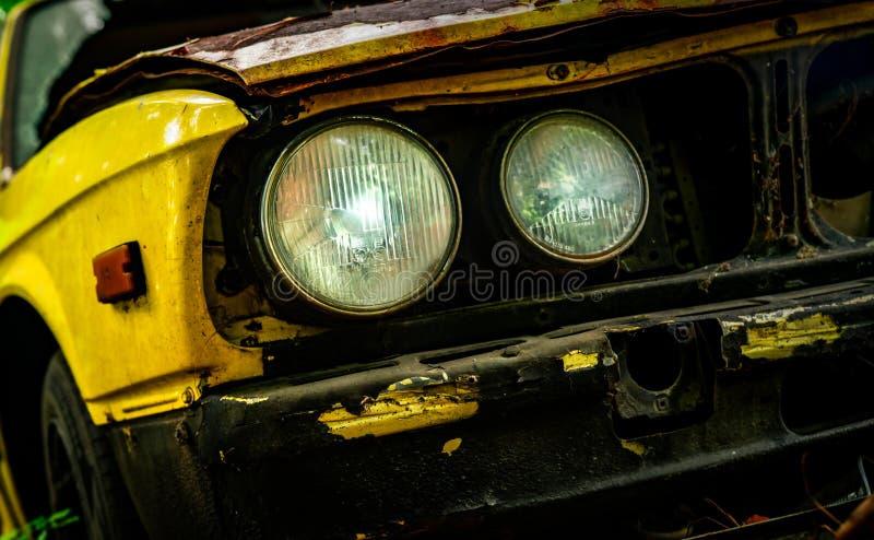 Vieille voiture détruite dans le style de vintage Voiture jaune rouillée abandonnée dans les phares de vue de face de plan rappro image libre de droits