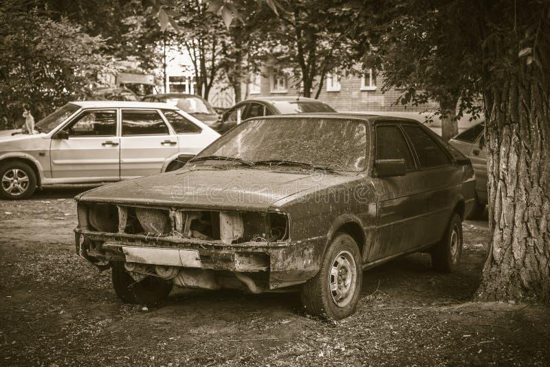 Vieille voiture endommagée de production dans la cour de ville photos libres de droits