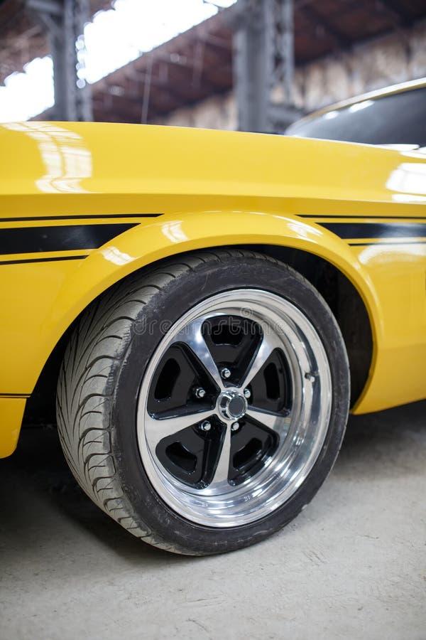 Vieille voiture jaune de muscle avec la roue d'alliage d'intérieur photos stock