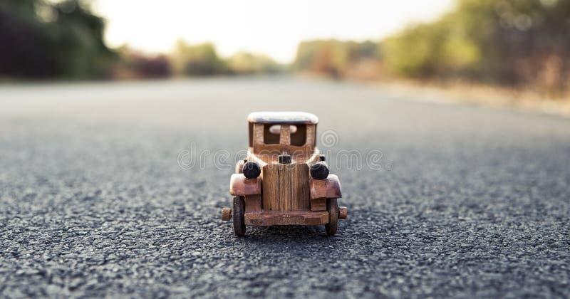 Vieille voiture-jouet en bois rétro sur la route photos stock