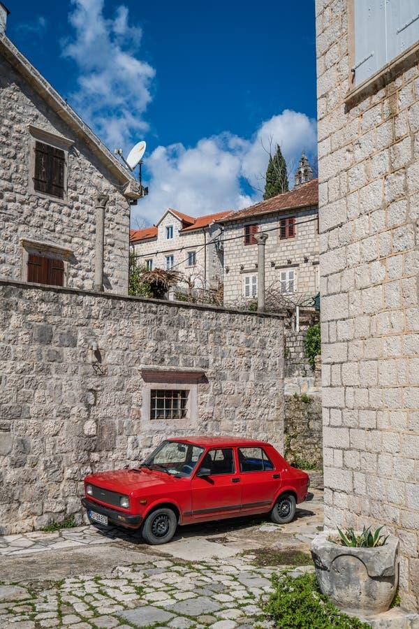 Vieille voiture rouge dans la ville de Perast images stock