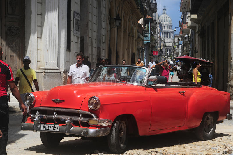 Vieille voiture rouge sur la rue crue à vieille La Havane image stock