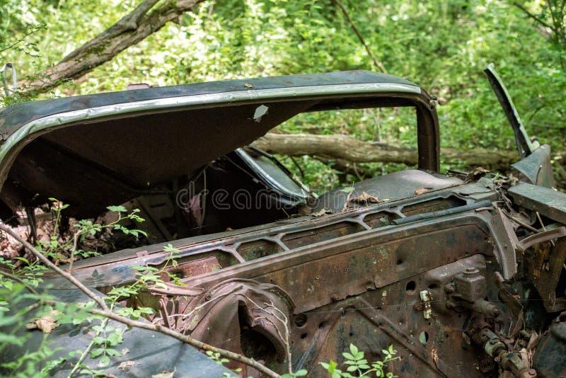 Vieille voiture rouillée abandonnée dans la forêt avec des trous de balle d'arme à feu photo stock