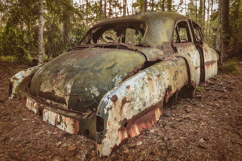 Vieille voiture rouillée de chute dans une forêt photographie stock libre de droits