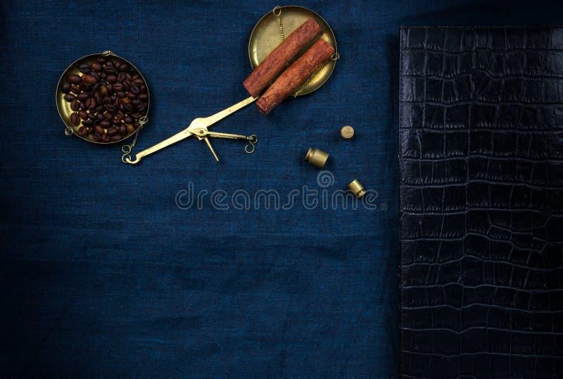 Vieilles échelles de manuel avec de petits poids et grains de café sur un tissu bleu images libres de droits