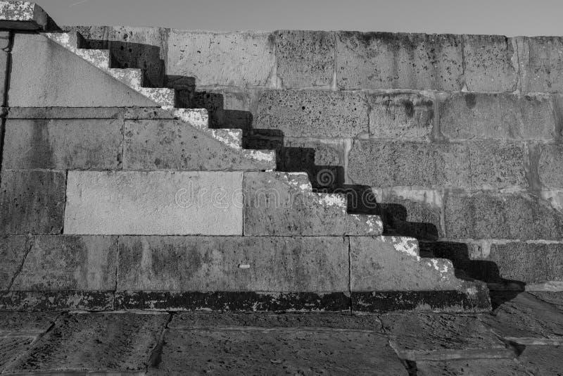 Vieilles étapes en pierre tirées en noir et blanc avec les ombres fortes contre le mur en pierre images stock