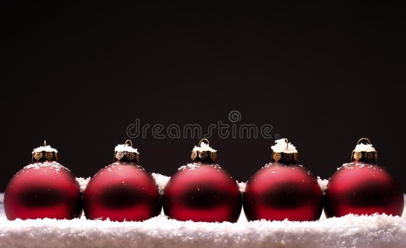 Vieilles babioles rouges de Noël avec la neige photo stock