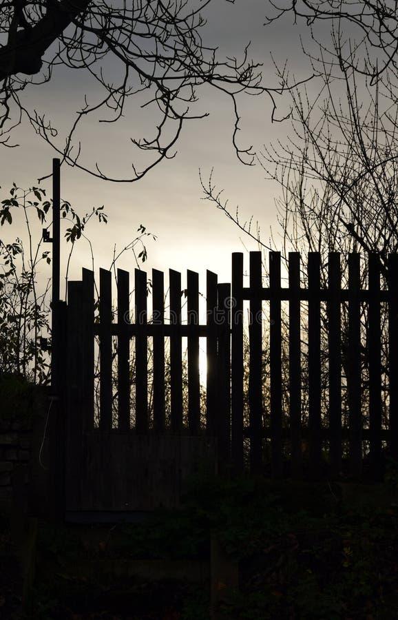 Vieilles barrière et porte en bois dans le coucher du soleil images libres de droits