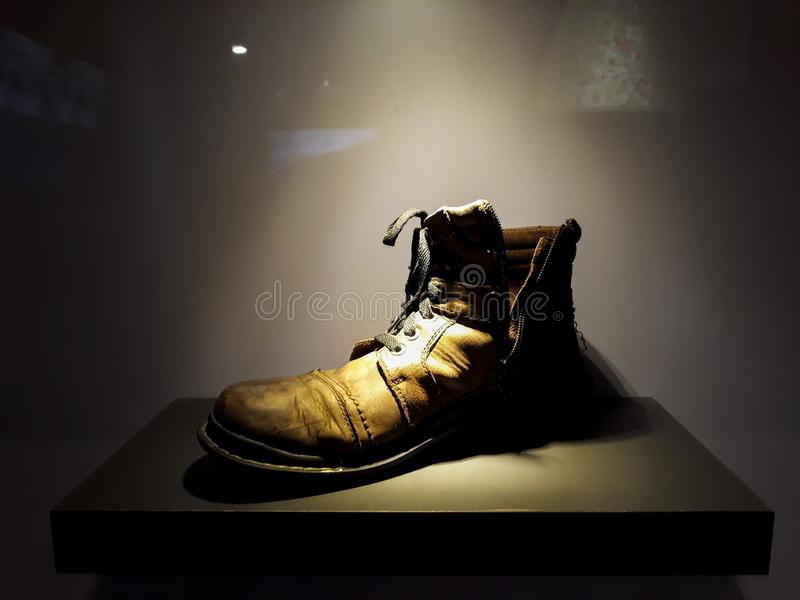 Vieilles bottes dans diplay avec l'éclairage sur le fond noir images libres de droits