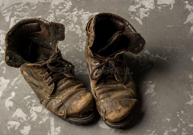 Vieilles bottes sur le fond concret, concept de cru photo stock