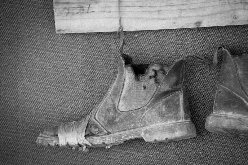 Vieilles bottes sur un fil réparé avec la bande photographie stock libre de droits