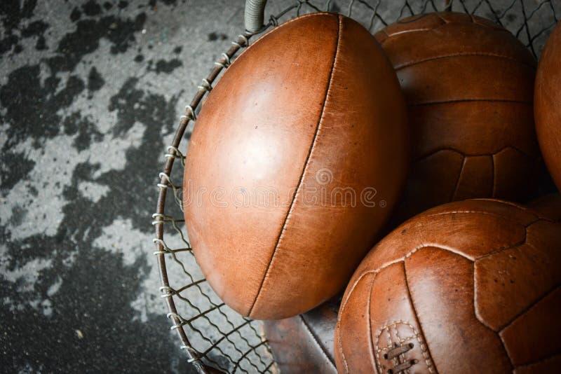 Vieilles boules en cuir dans un panier images stock