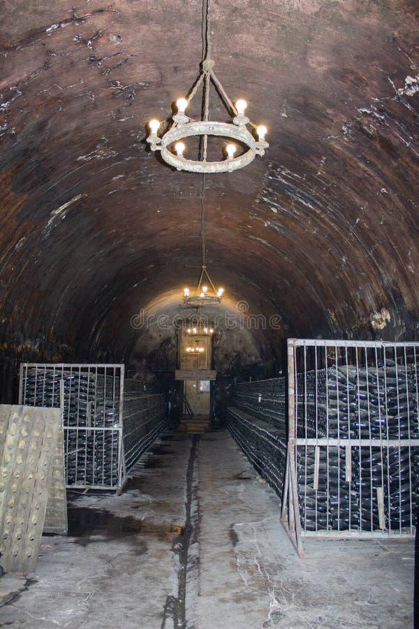 Vieilles bouteilles de vin rouge vieillissant dans une cave Vieille cave pour le stockage de vin photographie stock