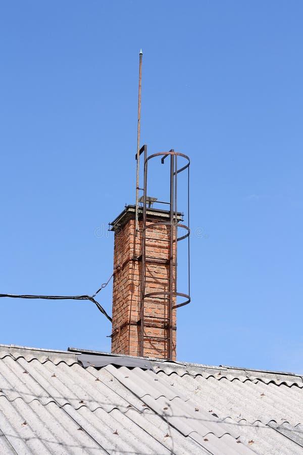 Vieilles cheminée et échelle sur le toit images libres de droits