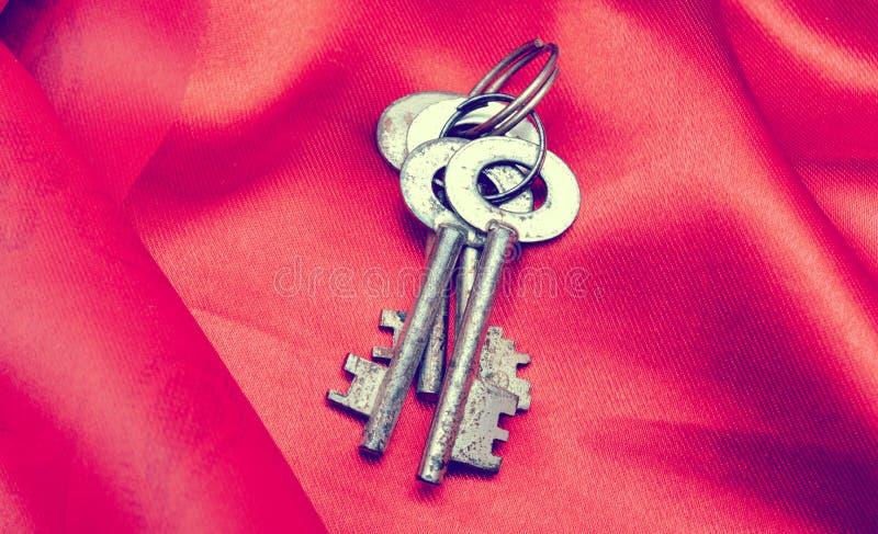 Vieilles clés de vintage sur le tissu rouge photos stock