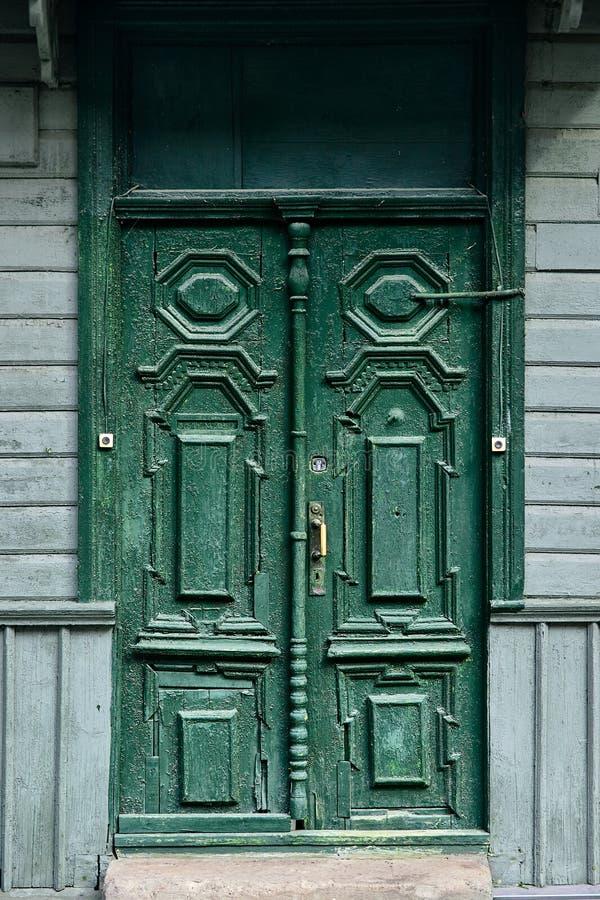 Vieilles cloches de porte découpées en bois peintes avec la peinture à l'huile verte avec la poignée en bronze et la serrure en a photo libre de droits