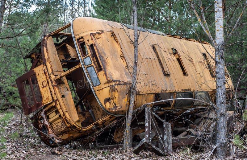 Vieilles configurations jaunes d'autobus de rouille abandonnées dans la forêt de zone d'exclusion de Chernobyl photographie stock libre de droits