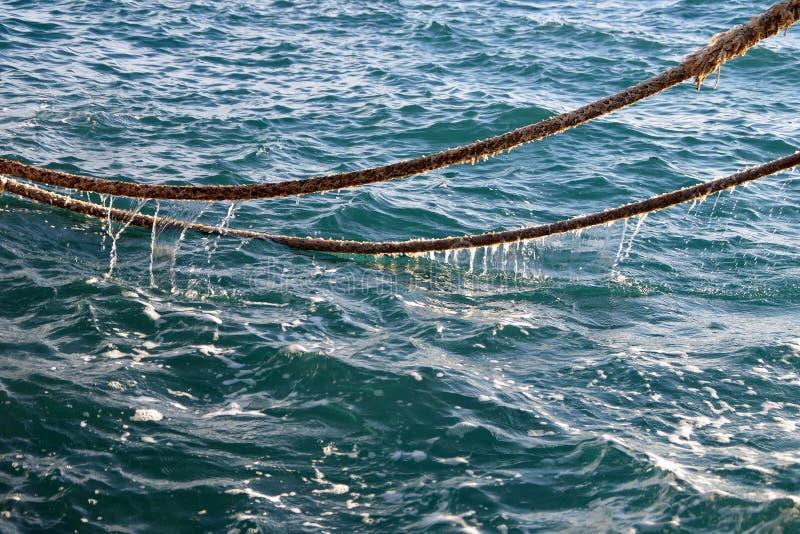 Vieilles cordes de bateau déchirées au-dessus de l'eau de mer images libres de droits