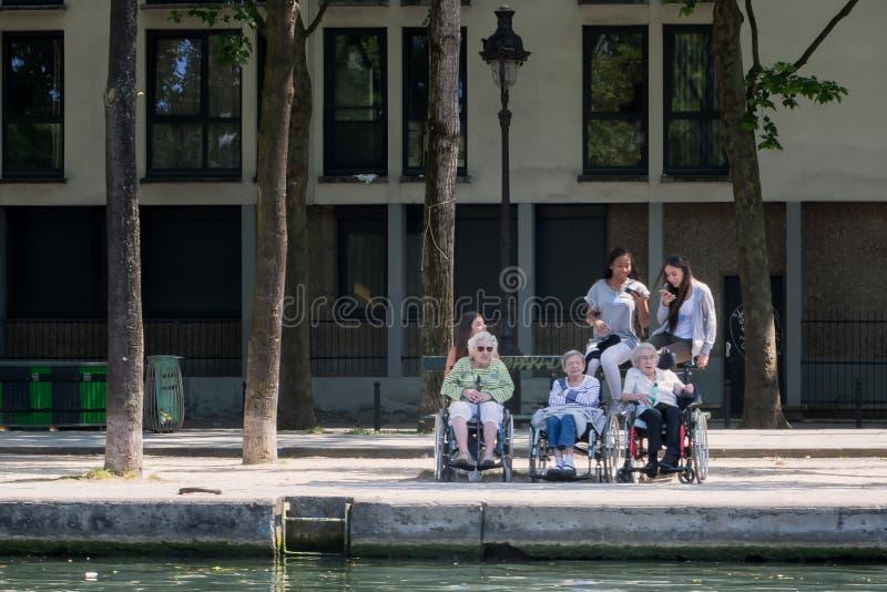 Vieilles femmes handicapées dans les fauteuils roulants et leurs jeunes aides photo libre de droits