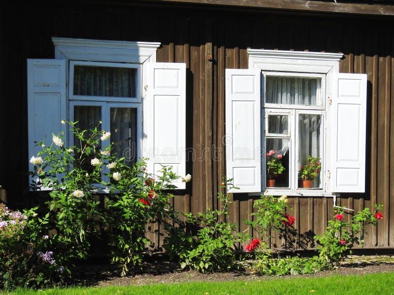 Vieilles fenêtres et fleurs à la maison, Lithuanie photos stock
