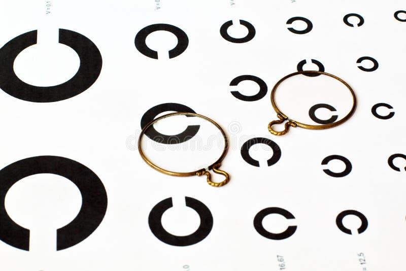 Vieilles lentilles antiques dans la jante de cuivre sur la table pour déterminer l'acuité visuelle rétro photo libre de droits