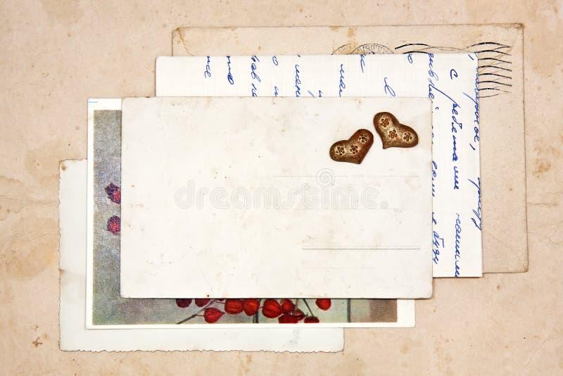 Vieilles lettres, cartes postales vides et deux coeurs image libre de droits